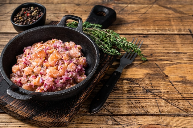 Tatar oder tatar mit lachsfisch, roten zwiebeln, rucola und kapern in einer pfanne