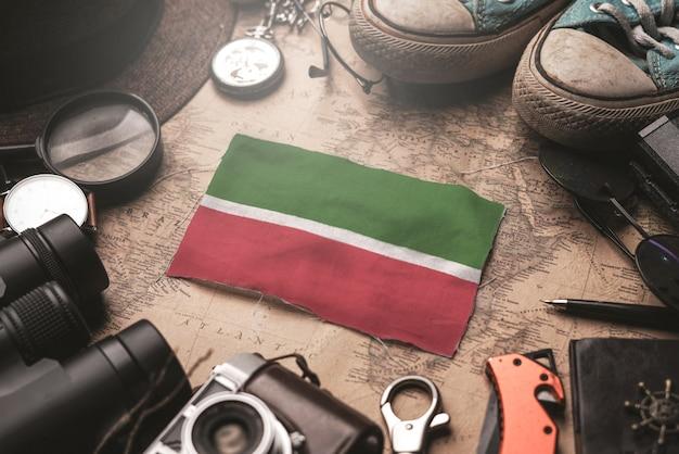 Tatarstan-flagge zwischen dem zubehör des reisenden auf alter weinlese-karte. touristisches bestimmungsort-konzept.