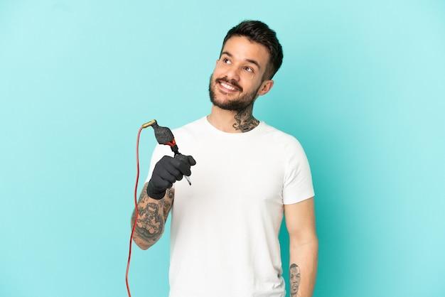 Tattoo-künstler mann über isolierte blauem hintergrund nach oben schauend, während er lächelt