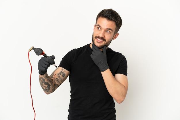 Tattoo-künstler mann über isolierten weißen hintergrund nach oben schauend, während er lächelt