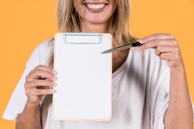 Taube frau, die etwas auf leerem weißbuch mit klemmbrett zeigt