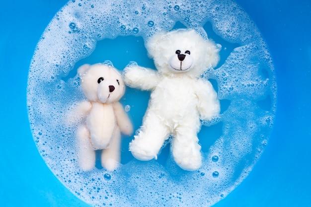 Tauchen sie zwei spielzeugbären vor dem waschen in waschmittelwasser.