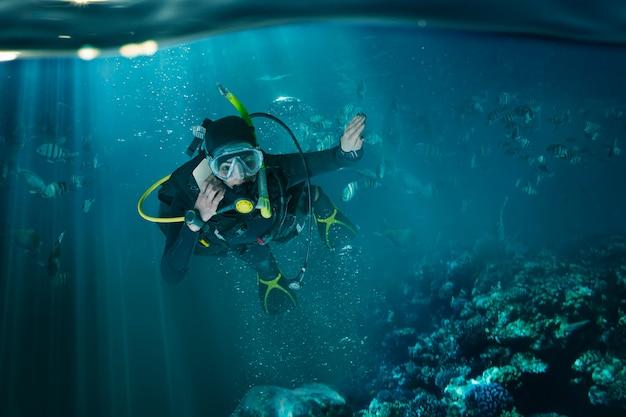 Taucher in neoprenanzug und tauchausrüstung, unterwasseransicht