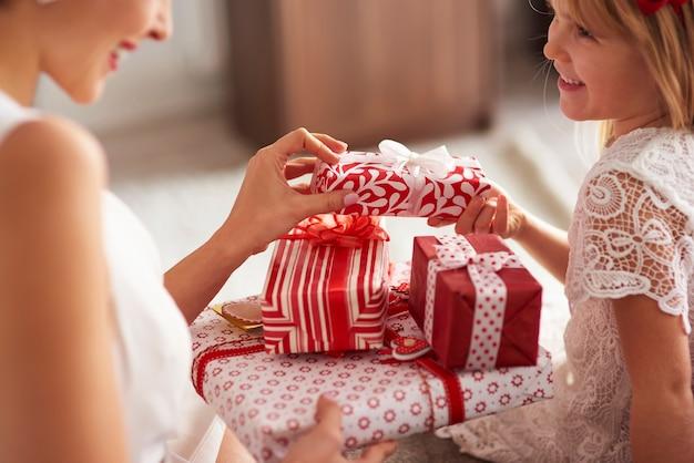 Tauschen sie geschenke zwischen frau und kleinem mädchen aus
