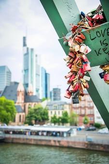 Tausende liebesvorhängeschlösser an der schiene der eisenbrücke in frankfurt um main.