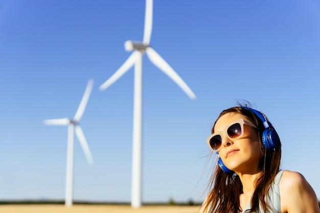 Tausendjährige frau, die den sonnenuntergang mit helmen und sonnenbrillen und windmühlen auf dem rücken genießt