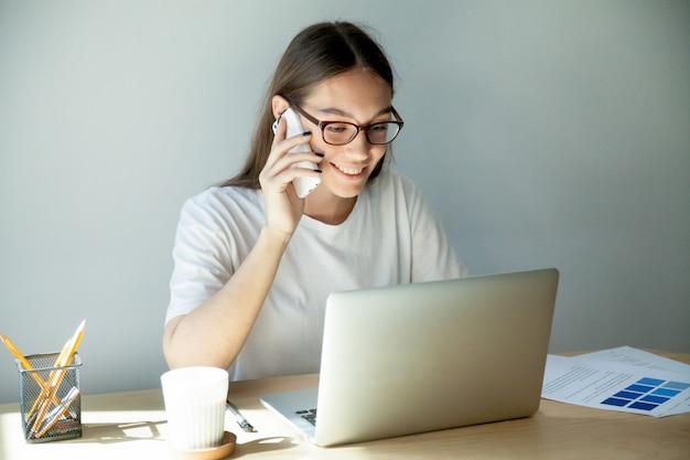 Tausendjährige frau in den gläsern sprechend auf mobile und mit laptop