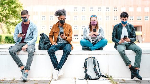 Tausendjährige freunde, die smartphones mit gesichtsmaske auf der zweiten welle von covid verwenden