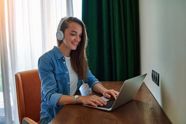 Tausendjährige glücklich lächelnde kaukasische freiberuflerin mit drahtlosen kopfhörern sitzt am schreibtisch im hotelzimmer und arbeitet mit laptop aus der ferne. machen sie einen online-kurs oder eine schulung zu hause