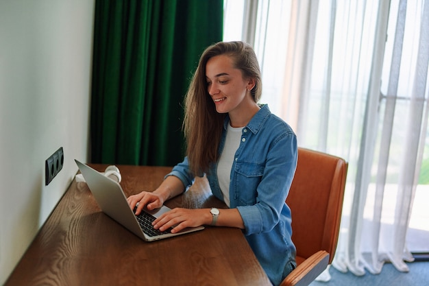 Tausendjährige glücklich lächelnde kaukasische freiberuflerin sitzt am schreibtisch im hotelzimmer und arbeitet mit laptop aus der ferne?