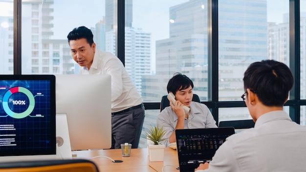 Tausendjährige gruppe junger asiatischer geschäftsleute in einem kleinen modernen büro. japanischer männlicher chef supervisor unterrichtet praktikant oder neuer mitarbeiter chinesischer junger mann, der bei schwieriger aufgabe im besprechungsraum hilft.