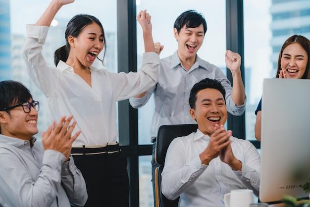 Tausendjährige gruppe junger geschäftsleute asiens geschäftsmann und geschäftsfrau feiern das geben von fünf, nachdem sie sich glücklich gefühlt und einen vertrag oder eine vereinbarung im besprechungsraum in einem kleinen modernen büro unterschrieben haben.