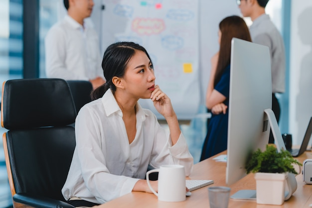 Tausendjährige junge chinesische geschäftsfrau, die stress mit projektforschungsproblem auf computer-desktop im besprechungsraum in kleinem modernem büro herausarbeitet. konzept des burnout-syndroms für menschen in asien.