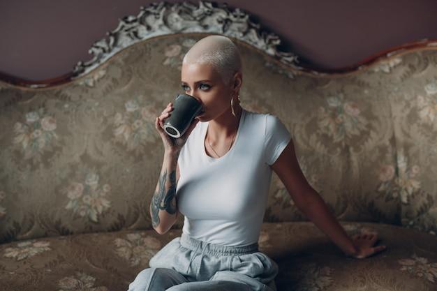Tausendjährige junge frau mit dem kurzen blonden haarporträt, das auf weinlesesofa sitzt.