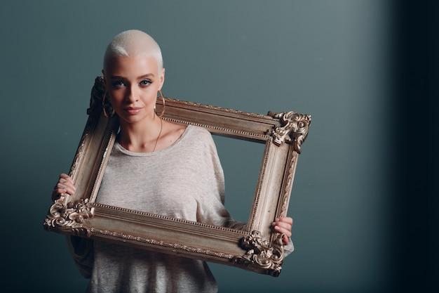 Tausendjährige junge frau mit kurzen blonden haaren hält vergoldeten bilderrahmen in den händen auf ihrem nacken-schulter-porträt
