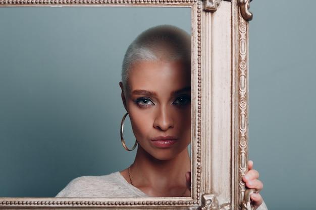 Tausendjährige junge frau mit kurzen blonden haaren hält vergoldeten bilderrahmen in den händen hinter ihrem gesichtsporträt