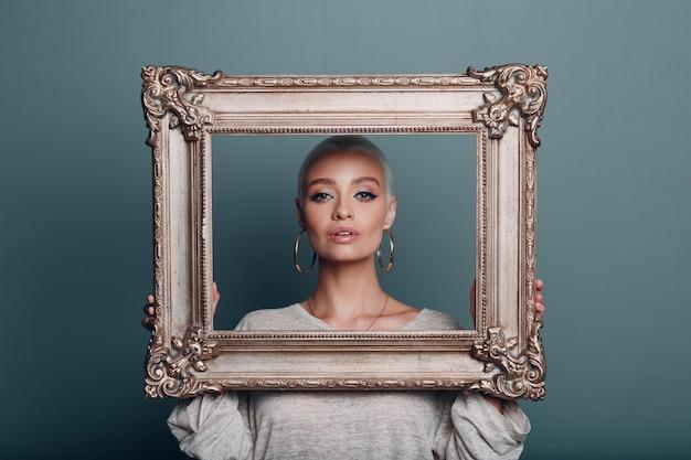 Tausendjährige junge frau mit kurzen blonden haaren hält vergoldeten bilderrahmen in den händen in der nähe ihres gesichtsporträts