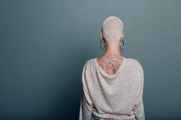 Tausendjährige junge frau mit kurzen blonden haaren hintere rückansicht stehen an der wand.