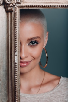 Tausendjährige junge frau mit kurzen blonden haaren vergoldeter bilderrahmen gesicht porträt