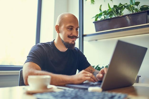 Tausendjähriger kaukasischer mann arbeitet am computer im homeoffice-fernjob