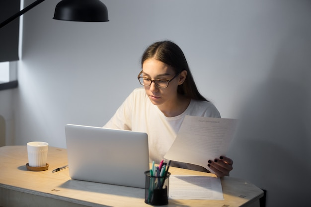 Tausendjähriger manager in den gläsern, die an laptop arbeiten und dokument halten