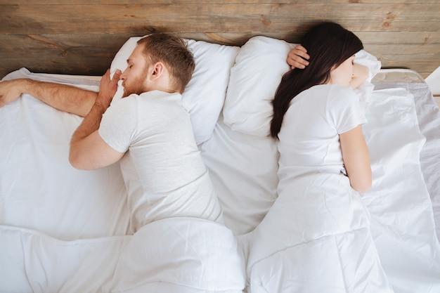 Tausendjähriger mann und frau, die zusammen ein nickerchen machen und im bett ruhen, während sie fest schlafen