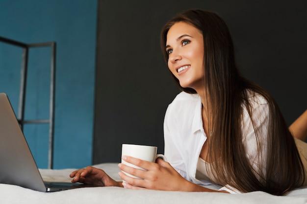 Tausendjähriges mädchen sitzt auf dem bett vor laptop in weißem hemd und hält tasse kaffee in der hand.