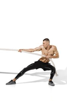 Tauziehen stilvoller junger männlicher athlet, der an weißer studiowand übt