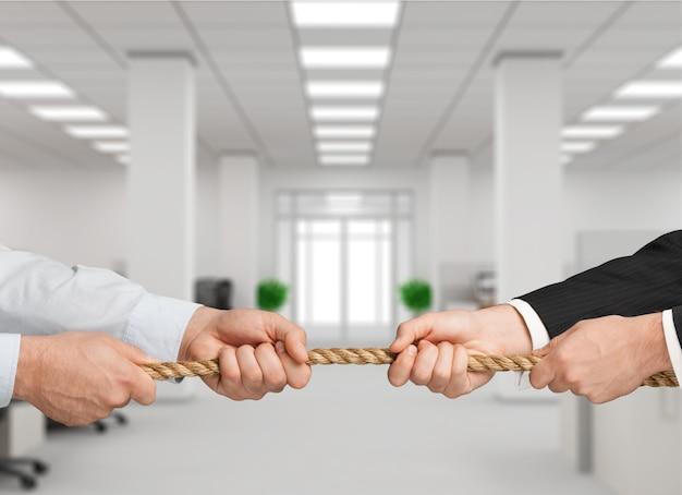 Tauziehen, zwei unternehmer ziehen ein seil in entgegengesetzte richtungen
