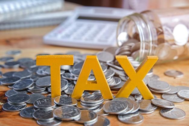 Tax concept.wort steuer mit gestapelten münzen gibt es einen notebook-rechner