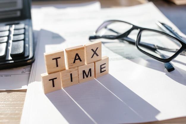 Tax time-holzbuchstaben mit steuerformular, brille und taschenrechner