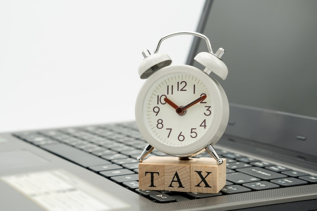 Tax time-uhren setzen auf das holzwort tax und die weiße tastatur