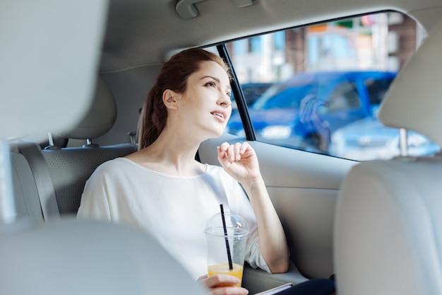 Taxifahrt. nachdenkliche kluge attraktive geschäftsfrau, die im auto sitzt und eine tasse mit saft hält, während sie zur arbeit geht