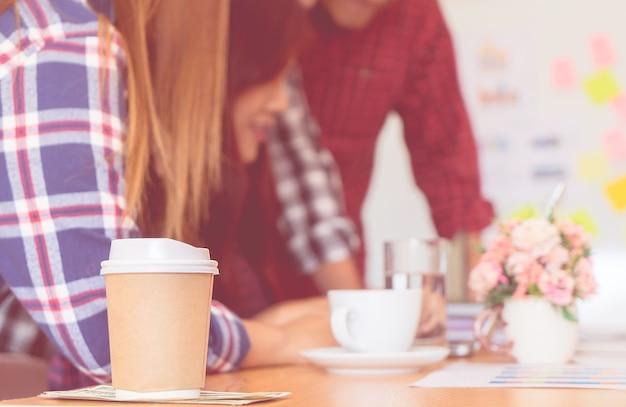 Team, das geschäftsdaten auf tabelle mit kaffee analysierend zusammenarbeitet