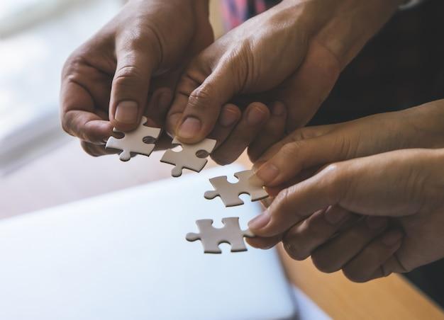 Team, das vier puzzlesäge für teamkonzept zusammen setzt