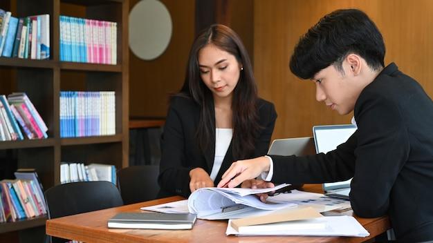 Team der personalabteilungen liest gemeinsam den lebenslauf zur auswahl neuer personalvertreter.
