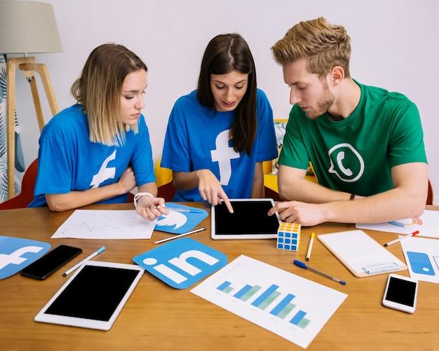 Team der social media-vernetzung, die digitale tablette im büro betrachtet