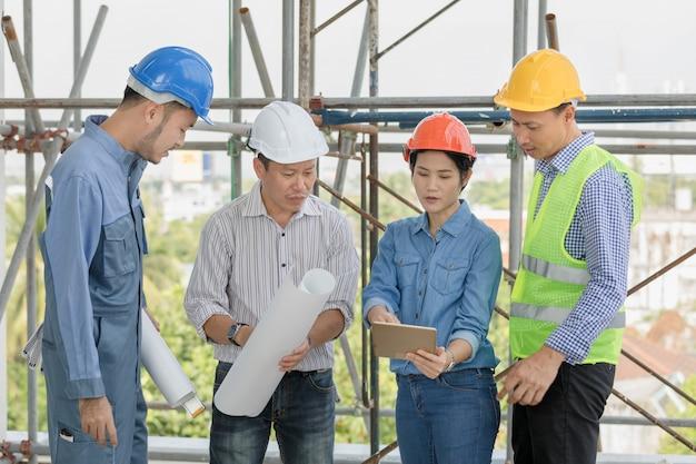 Team des ingenieurs und der architekten, die plangebäude im tablet-computer an der baustelle besprechen