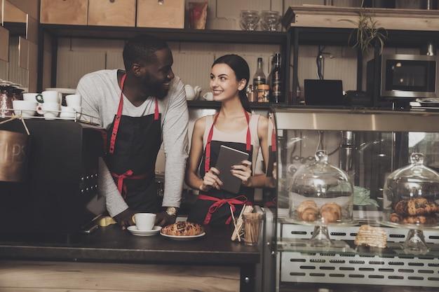 Team des männlichen und weiblichen barista-servicekunden