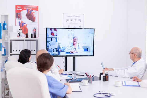 Team des medizinischen personals während der videokonferenz mit dem arzt im besprechungsraum des krankenhauses. medizinpersonal, das das internet während des online-meetings mit einem erfahrenen arzt nutzt, um fachwissen zu erhalten.