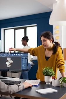 Team diskutiert über ein industrieprojekt mit dual-monitor-setup zum entwerfen von 3d-zahnrädern und metallklammern in cad-software