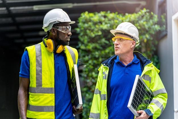 Team fabrikarbeiter techniker ingenieur männer in grünem arbeitsanzug kleid und schutzhelm sprechen und halten solarpanel.