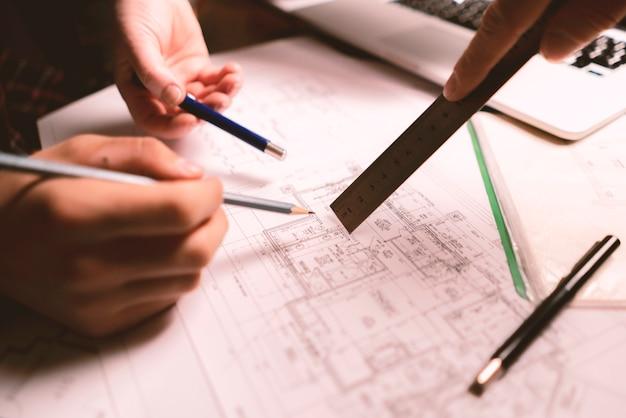 Team freundlicher architekten, die einen bauplan erstellen