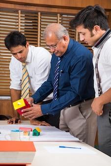 Team indischer architekten oder bauherren, die ein wohnprojekt mit dem gebäudemodell entwerfen oder diskutieren und um einen konferenztisch planen, selektiver fokus