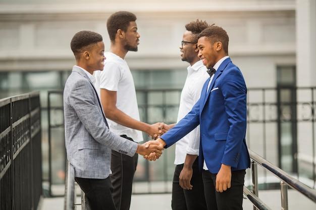 Team junger afrikanischer männer in der nähe des gebäudes geben sich die hand