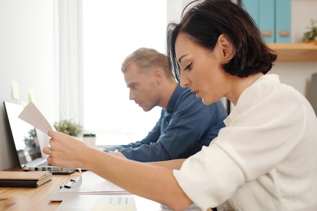 Team junger geschäftsleute, die projektdokumente und -berichte korrektur lesen und prüfen