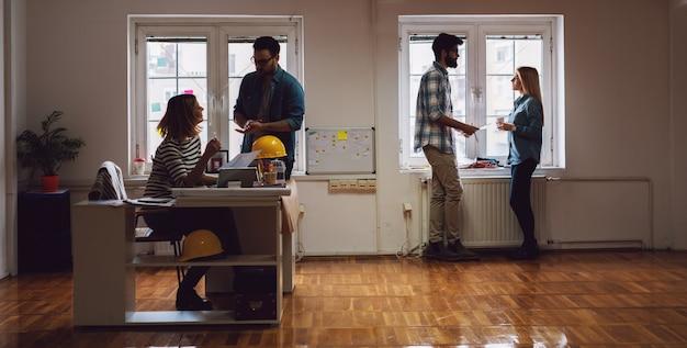 Team junger moderner ingenieure, die im büro zusammenarbeiten.