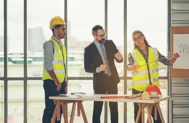 Team multiethnischer architekten, die im besprechungsraum an bauplänen arbeiten. ingenieure diskutieren über projekt im büro. reifer geschäftsmann und frau, die um tisch stehen, der an blaupause arbeitet.