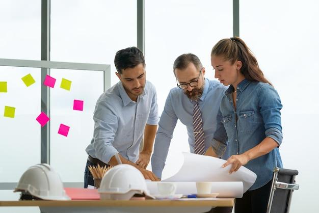 Team multiethnischer architekten, die im besprechungsraum an bauplänen arbeiten. ingenieure diskutieren über projekt im büro.