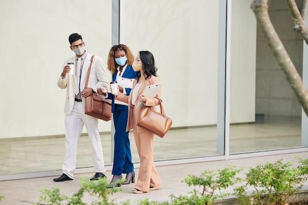 Team selbstbewusster erfolgreicher geschäftsleute, die mit schutzmasken die straße entlang gehen, kaffee trinken und über die arbeit diskutieren
